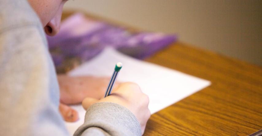 estudante escrevendo em uma folha